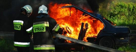 Dwoje strażaków gasi palący się samochód